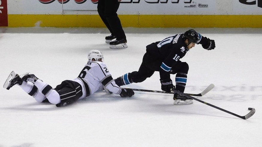 San Jose Sharks center Andrew Desjardins (10) skates past Los Angeles Kings defenseman Slava Voynov (26), from Russia, during the first period of an NHL hockey game in San Jose, Calif., Thursday, April 3, 2014. (AP Photo/Jeff Chiu)