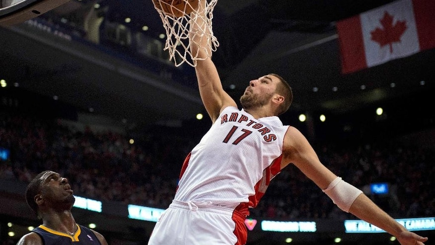 Toronto Raptors center Jonas Valanciunas (17) dunks against Indiana Pacers center Roy Hibbert during the first half of an NBA basketball game Friday, April 4, 2014, in Toronto. (AP Photo/The Canadian Press, Frank Gunn)