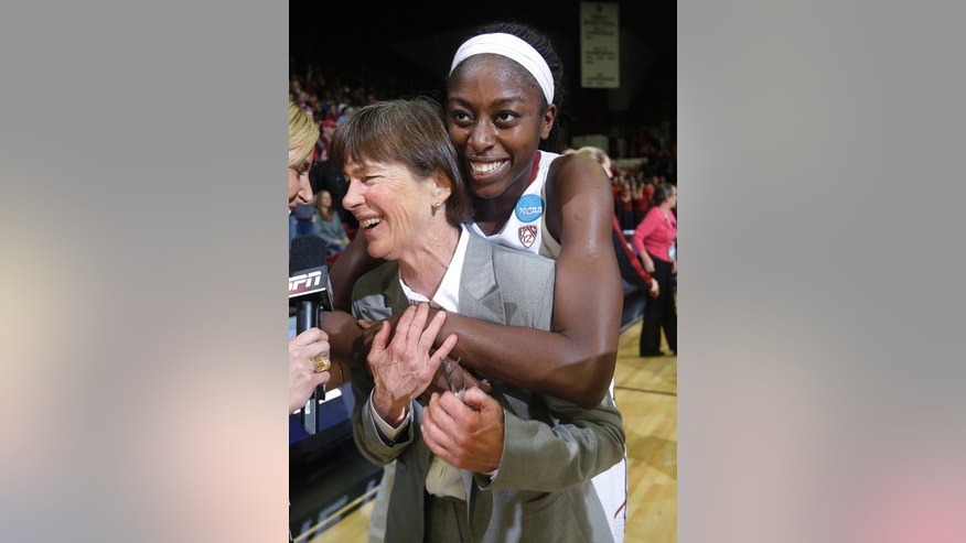 Stanford coach Tara VanDerveer is hugged by forward Chiney Ogwumike, rear, during an interview after a regional final against North Carolina in the NCAA women's college basketball tournament in Stanford, Calif., Tuesday, April 1, 2014. Stanford won 74-65. (AP Photo/Marcio Jose Sanchez)