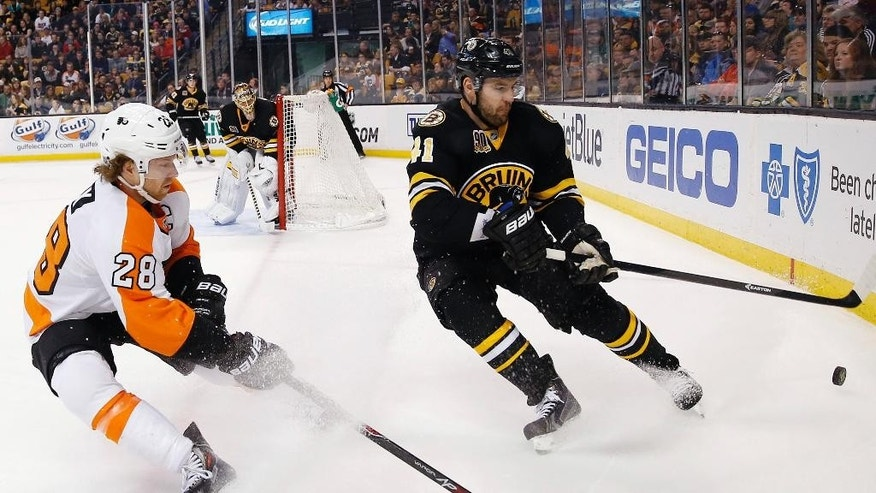 Philadelphia Flyers' Claude Giroux (28) and Boston Bruins' Andrej Meszaros (41) battle for the puck in the first period of an NHL hockey game in Boston, Saturday, April 5, 2014. (AP Photo/Michael Dwyer)