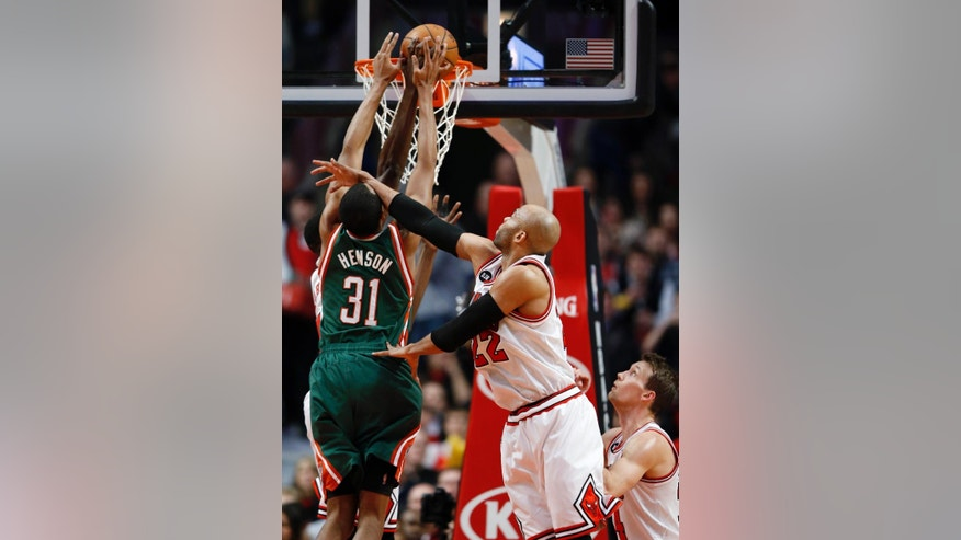 Chicago Bulls center Nazr Mohammed, back, and forward Taj Gibson (22), defend Milwaukee Bucks forward John Henson (31) during the first half of an NBA basketball game in Chicago, Friday, April 4, 2014. (AP Photo/Kamil Krzaczynski)