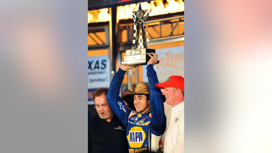 Chase Elliott holds up the trophy in Victory Lane after winning the NASCAR Nationwide Series auto race at Texas Motor Speedway in Fort Worth, Texas, Friday, April 4, 2014. (AP Photo/Ralph Lauer)