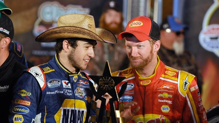 Chase Elliott, left, talks with team owner Dale Earnhardt Jr. in Victory Lane after Elliot won the NASCAR Nationwide Series auto race at Texas Motor Speedway in Fort Worth, Texas, Friday, April 4, 2014. (AP Photo/Ralph Lauer)