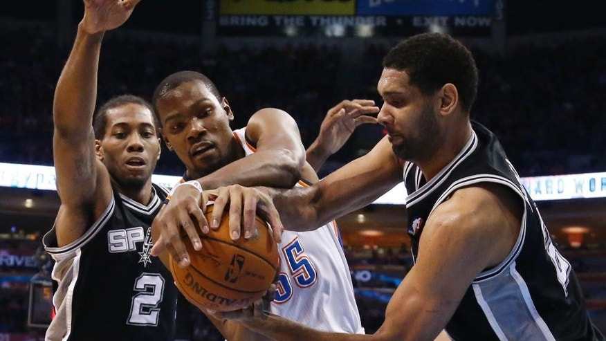 Oklahoma City Thunder forward Kevin Durant (35) and San Antonio Spurs forward Tim Duncan, right, vie for control of the ball in front of Spurs forward Kawhi Leonard (2) during the first quarter of an NBA basketball game in Oklahoma City, Thursday, April 3, 2014. (AP Photo/Sue Ogrocki)