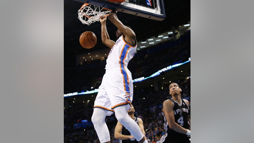 Oklahoma City Thunder forward Kevin Durant (35) dunks in front of San Antonio Spurs guard Tony Parker and guard Danny Green (4) in the second quarter of an NBA basketball game in Oklahoma City, Thursday, April 3, 2014. (AP Photo/Sue Ogrocki)