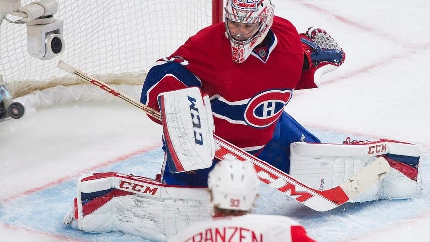 Montreal Canadiens goaltender Carey Price makes a save against Detroit Red Wings' Johan Franzen during the second period of an NHL hockey game in Montreal, Saturday, April 5, 2014. (AP Photo/The Canadian Press, Graham Hughes)