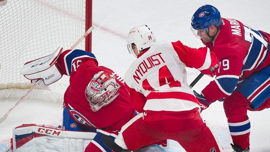 Montreal Canadiens goaltender Carey Price left, makes a save against Detroit Red Wings' Gustav Nyquist, center, as Canadiens' Andrei Markov during the second period of an NHL hockey game in Montreal, Saturday, April 5, 2014. (AP Photo/The Canadian Press, Graham Hughes)