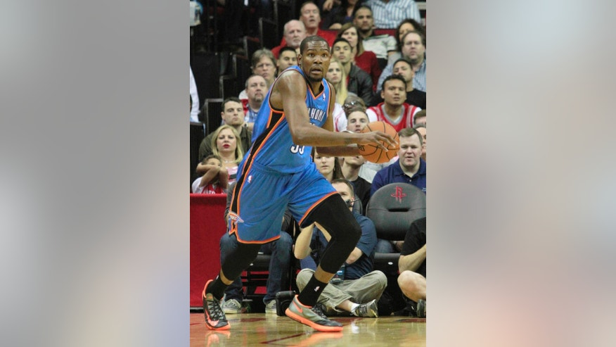 Oklahoma City Thunder forward Kevin Durant looks up court after grabbing a rebound against the Houston Rockets during an NBA basketball game in Houston Friday, April 4, 2014.   (AP Photo/Richard Carson)