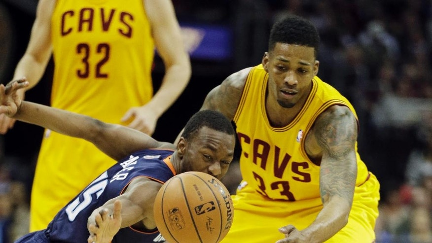 Charlotte Bobcats' Kemba Walker, front left, knocks the ball away from Cleveland Cavaliers' Alonzo Gee (33) in the second quarter of an NBA basketball game on Saturday, April 5, 2014, in Cleveland. (AP Photo/Mark Duncan)