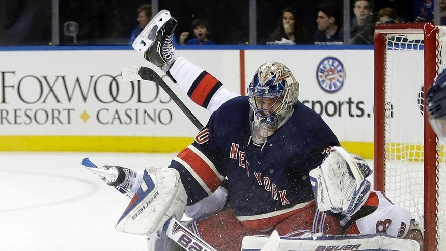 New York Rangers goalie Henrik Lundqvist (30), of Sweden, stops a shot on the goal by Ottawa Senators' Ales Hemsky (83) who flipped over him on the play during the first period of an NHL hockey game Saturday, April 5, 2014, in New York. (AP Photo/Frank Franklin II)