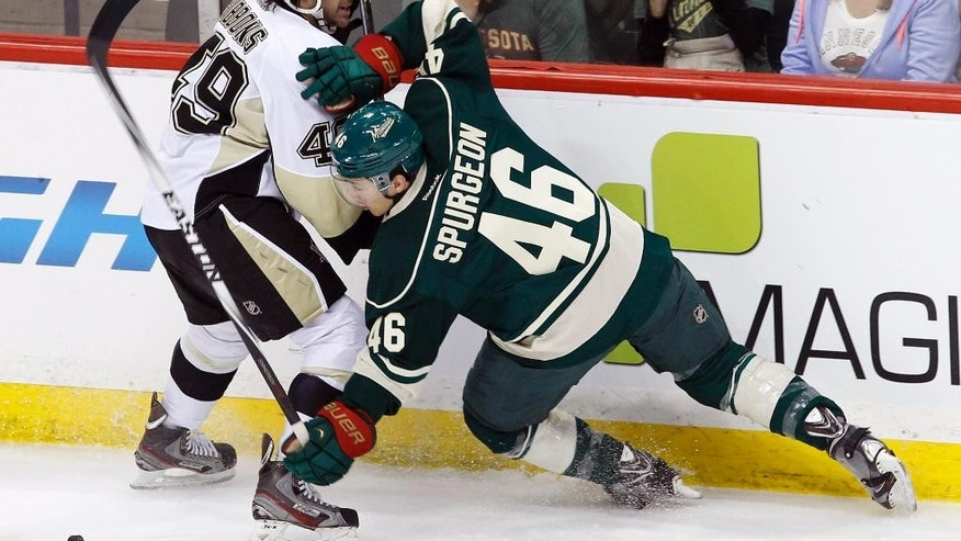 Minnesota Wild defenseman Jared Spurgeon (46) falls as he and Pittsburgh Penguins center Brian Gibbons (49) chase the puck during the first period of an NHL hockey game in St. Paul, Minn., Saturday, April 5, 2014. (AP Photo/Ann Heisenfelt)