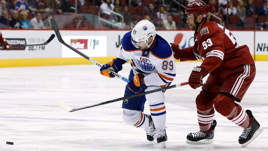 Edmonton Oilers' Sam Gagner (89) skates in front of Phoenix Coyotes' Derek Morris (53) during the first period of an NHL hockey game, Friday, April 4, 2014, in Glendale, Ariz. (AP Photo/Ross D. Franklin)