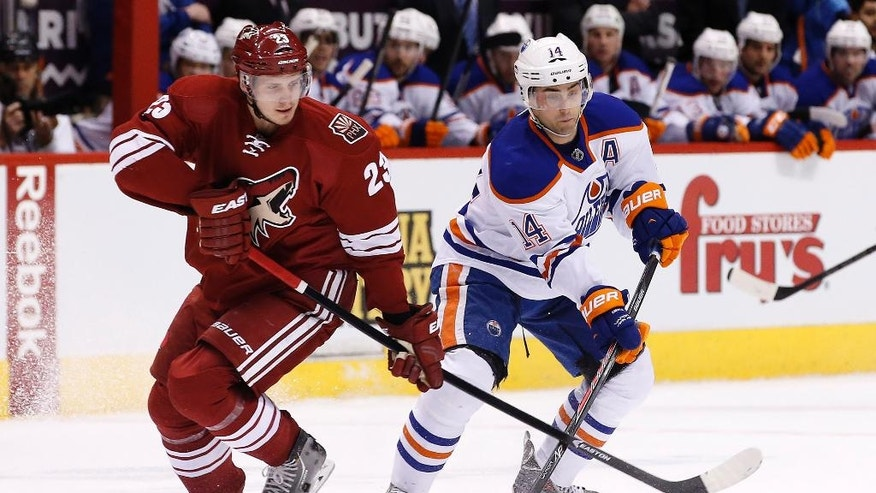 Phoenix Coyotes' Oliver Ekman-Larsson (23), of Sweden, slaps the stick of Edmonton Oilers' Jordan Eberle (14) as Eberle tries to make a pass during the first period of an NHL hockey game, Friday, April 4, 2014, in Glendale, Ariz. (AP Photo/Ross D. Franklin)