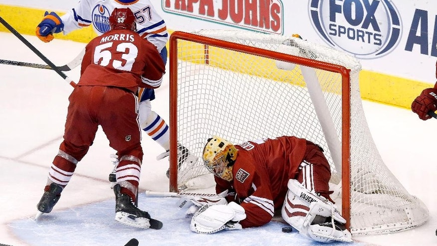 Phoenix Coyotes' Thomas Greiss, right, of Germany, makes a save on a shot by Edmonton Oilers' David Perron (57) as Coyotes' Derek Morris (53) defends during the second period of an NHL hockey game, Friday, April 4, 2014, in Glendale, Ariz. (AP Photo/Ross D. Franklin)