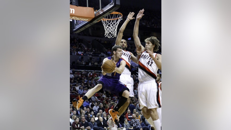 Phoenix Suns guard Goran Dragic, left, from Slovenia, looks to pass against Portland Trail Blazers' Robin Lopez, right, and Nicolas Batum, from France, during the first half of an NBA basketball game in Portland, Ore., Friday, April 4, 2014. (AP Photo/Don Ryan)