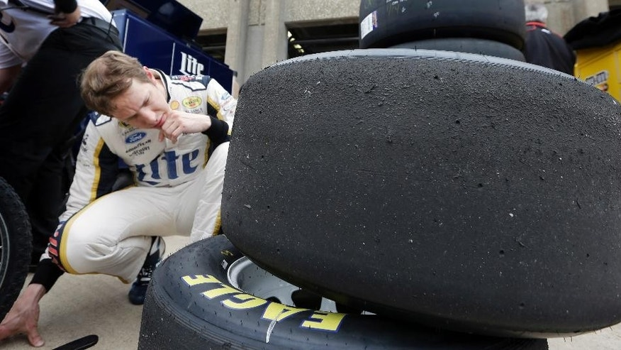 Brad Keselowski examines wear on tires he used during a practice session for the NASCAR Sprint Cup Series auto race at Texas Motor Speedway in Fort Worth, Texas, Saturday, April 5, 2014. (AP Photo/LM Otero)