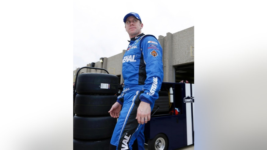 Carl Edwards leaves the garage heading to his trailer after a practice session for the NASCAR Sprint Cup Series auto race at Texas Motor Speedway in Fort Worth, Texas, Saturday, April 5, 2014. (AP Photo/LM Otero)