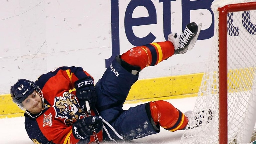 Florida Panthers center Vincent Trocheck (67) passes the puck as he falls to the ice during the first period of an NHL hockey game against the Dallas Stars in Sunrise, Fla., Sunday, April 6, 2014. (AP Photo/Terry Renna)