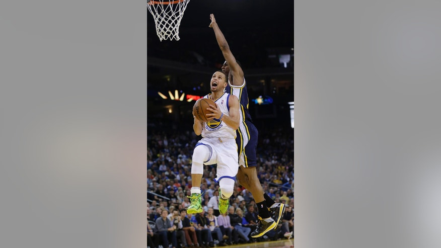 Golden State Warriors guard Stephen Curry scores past Utah Jazz guard Alec Burks during the first half of an NBA basketball game Sunday, April 6, 2014, in Oakland, Calif. (AP Photo/Marcio Jose Sanchez)