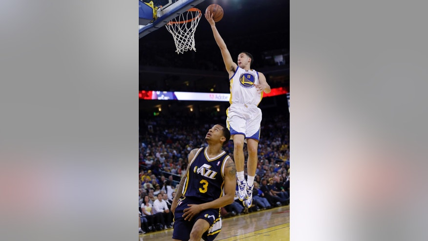 Golden State Warriors guard Klay Thompson (11) scores over Utah Jazz guard Trey Burke (3) during the first half of an NBA basketball game Sunday, April 6, 2014, in Oakland, Calif. (AP Photo/Marcio Jose Sanchez)