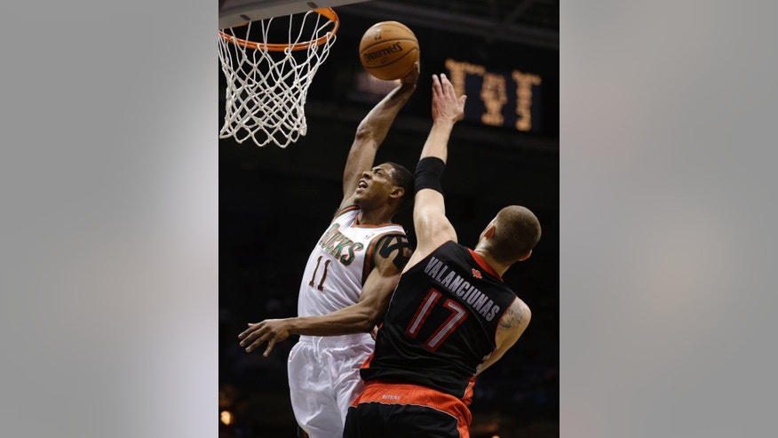 Milwaukee Bucks' Brandon Knight (11) dunks against Toronto Raptors' Jonas Valanciunas (17) during the second half of an NBA basketball game Saturday, April 5, 2014, in Milwaukee. (AP Photo/Jeffrey Phelps)