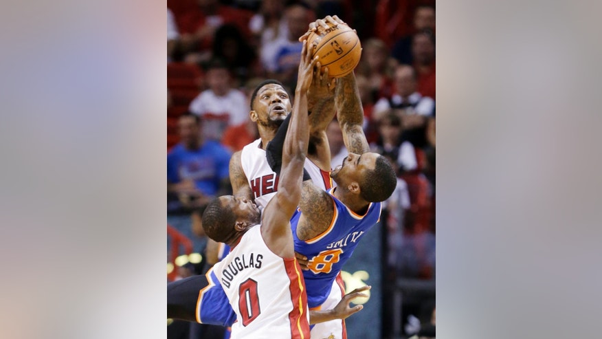 Miami Heat forward Udonis Haslem, rear, and guard Toney Douglas (0) prevent a pass by New York Knicks guard J.R. Smith (8) during the first half of an NBA basketball game, Sunday, April 6, 2014, in Miami. (AP Photo/Wilfredo Lee)
