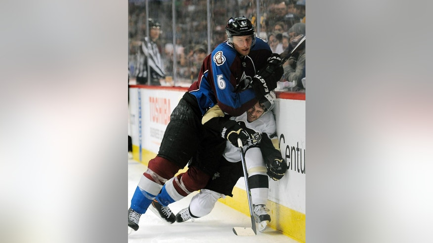 Colorado Avalanche defenseman Erik Johnson, top, checks Pittsburgh Penguins center Brian Gibbons against the boards during the second period of an NHL hockey game Sunday, April 6, 2014, in Denver.  (AP Photo/Chris Schneider)