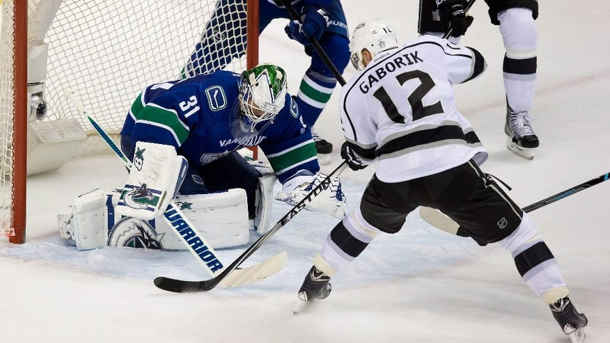 Vancouver Canucks' goalie Eddie Lack, left, of Sweden, stops Los Angeles Kings' Marian Gaborik, of Slovakia, during second period NHL hockey action in Vancouver, British Columbia, on Saturday April 5, 2014. (AP Photo/The Canadian Press, Darryl Dyck)