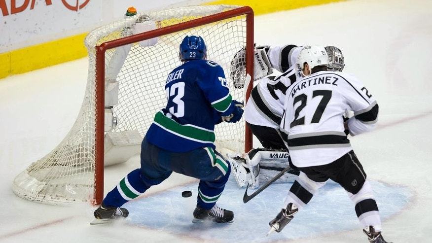 Vancouver Canucks' Alexander Edler, left, of Sweden, scores against Los Angeles Kings goalie Jonathan Quick, back, as Alec Martinez (27) defends during the third period of an NHL hockey game Saturday, April 5, 2014, in Vancouver, British Columbia. Vancouver won 2-1. (AP Photo/The Canadian Press, Darryl Dyck)