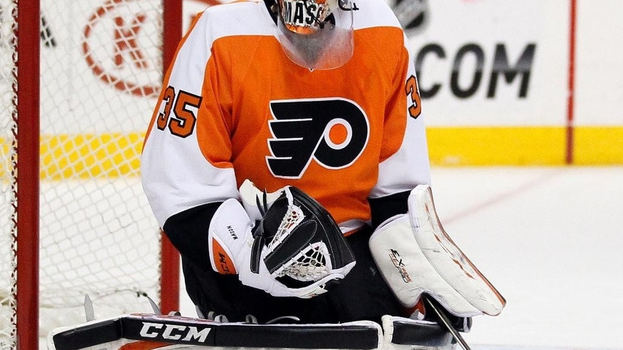 Philadelphia Flyers' Steve Mason watches the puck fly past during the first period of an NHL hockey game against the Buffalo Sabres, Sunday, April 6, 2014, in Philadelphia. (AP Photo/Tom Mihalek)