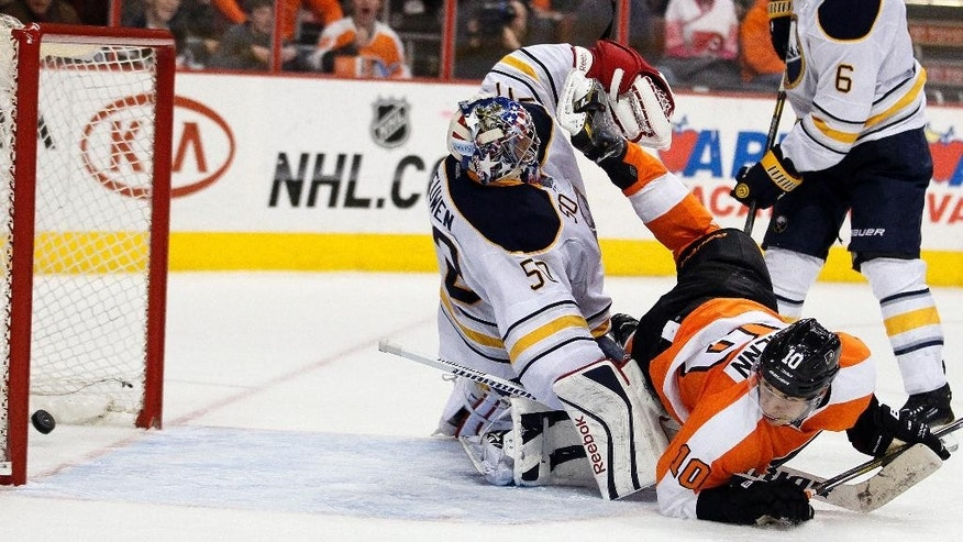 Philadelphia Flyers' Brayden Schenn, right, looks back to see his shot go in the net past Buffalo Sabres goalie Nathan Lieuwen, left, during the second period of an NHL hockey game, Sunday, April 6, 2014, in Philadelphia. (AP Photo/Tom Mihalek)