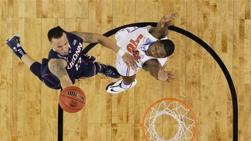 Connecticut guard Shabazz Napier, left, drives to the basket over Florida forward Dorian Finney-Smith during the first half of an NCAA Final Four tournament college basketball semifinal game Saturday, April 5, 2014, in Arlington, Texas. (AP Photo/David J. Phillip)