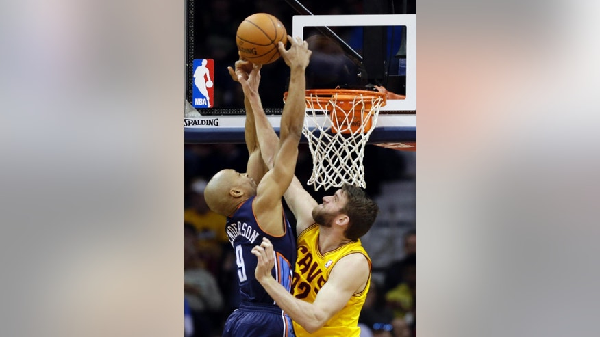 Cleveland Cavaliers' Spencer Hawes, right, fouls Charlotte Bobcats' Gerald Henderson (9) in the second quarter of an NBA basketball game on Saturday, April 5, 2014, in Cleveland. (AP Photo/Mark Duncan)