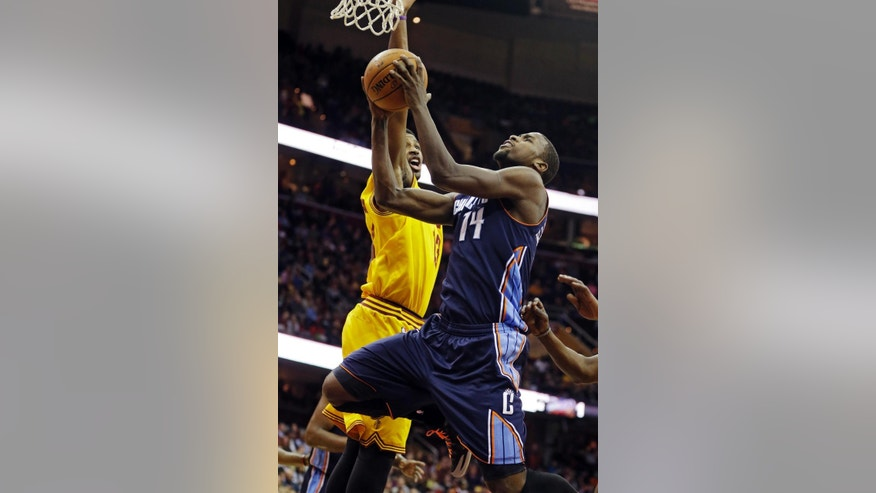 Charlotte Bobcats' Michael Kidd-Gilchrist (14) goes up to shoot  against Cleveland Cavaliers' Tristan Thompson in the first quarter of an NBA basketball game on Saturday, April 5, 2014, in Cleveland. (AP Photo/Mark Duncan)