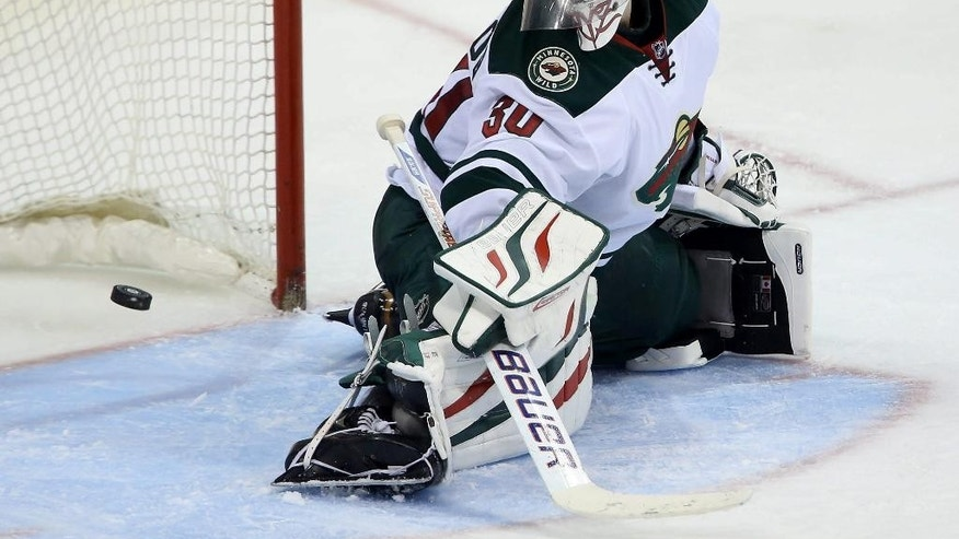 Minnesota Wild's Ilya Bryzgalov (30) makes a pad save during third period NHL hockey action against the Winnipeg Jets at in Winnipeg, Manitoba, Monday, April 7, 2014. (AP Photo/The Canadian Press, Trevor Hagan)