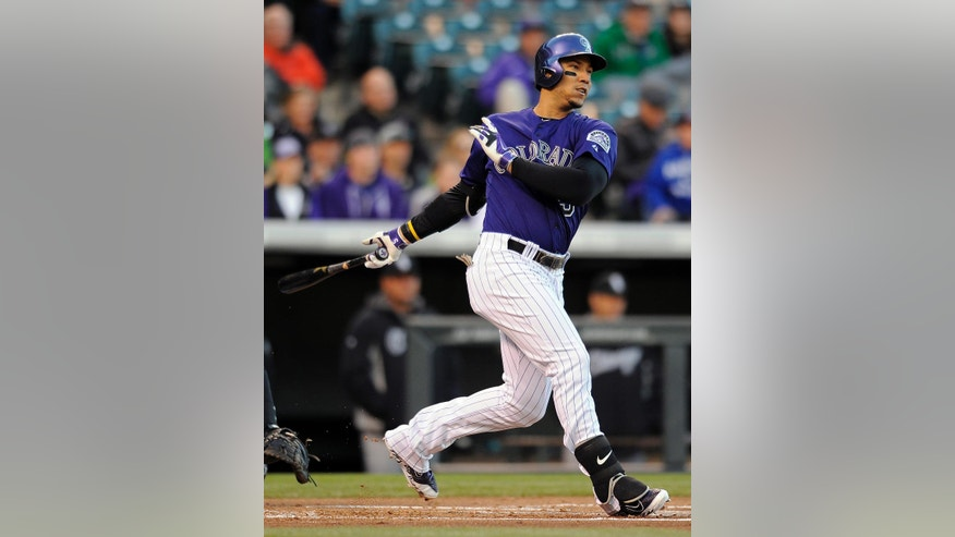 Colorado Rockies Carlos Gonzalez hits a solo home run in the first inning of a baseball game against  the Chicago White Sox on Monday, April 7, 2014, in Denver.(AP Photo/Chris Schneider)