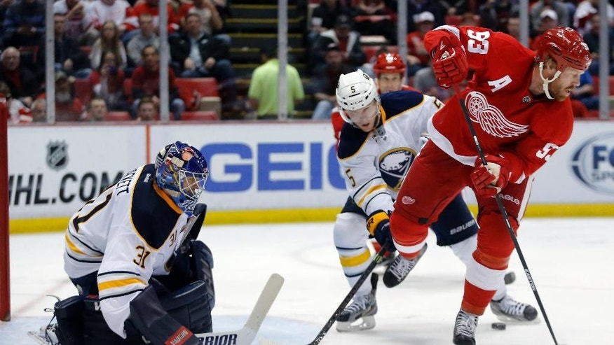 Detroit Red Wings' Johan Franzen (93), of Sweden, tries a back-hand pass against Buffalo Sabres' Chad Ruhwedel (5) while in front of Buffalo Sabres goalie Matt Hackett (31) during the second period of an NHL hockey game Friday, April 4, 2014, in Detroit. (AP Photo/Duane Burleson)