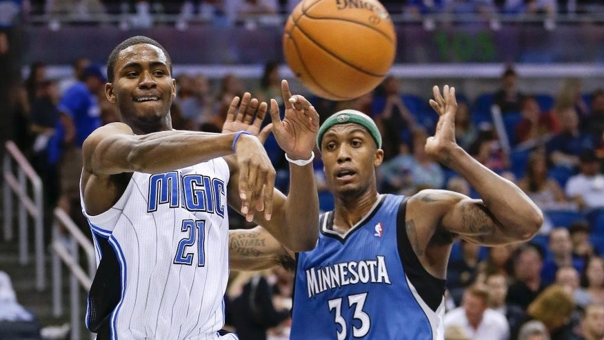 Orlando Magic's Maurice Harkless (21) passes the ball around Minnesota Timberwolves' Dante Cunningham (33) during the second half of an NBA basketball game in Orlando, Fla., Saturday, April 5, 2014. Orlando won 100-92. (AP Photo/John Raoux)