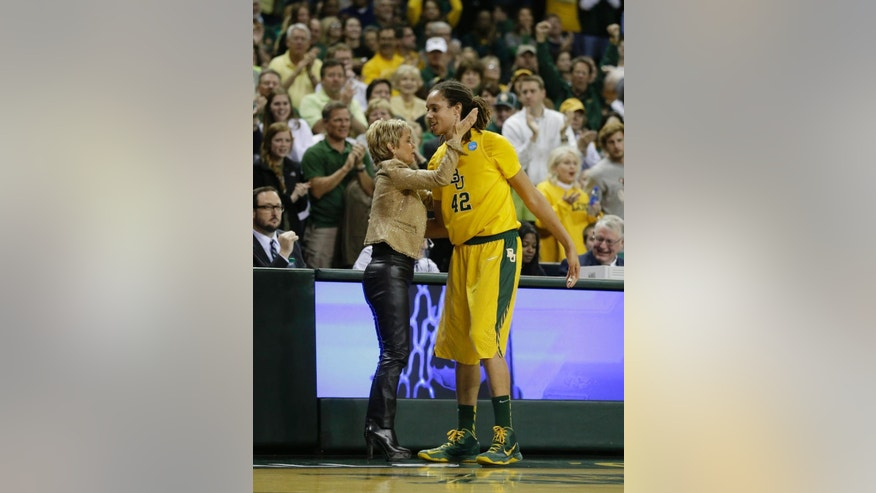 "FILE - In this March 26, 2013, file photo, Baylor head coach Kim Mulkey embraces Brittney Griner (42) as Griner leaves the game late in the second half of a second-round game against Florida State in the women's NCAA college basketball tournament in Waco, Texas. Griner's busy WNBA offseason included competing in China, her first vacation in Miami and courtside seats to watch favorite player LeBron James. The slam-dunking Griner can add published author to her list of achievements with ""In My Skin,"" which chronicles her love of basketball and struggles with bullying, sexuality and family acceptance. (AP Photo/Tony Gutierrez, File)"