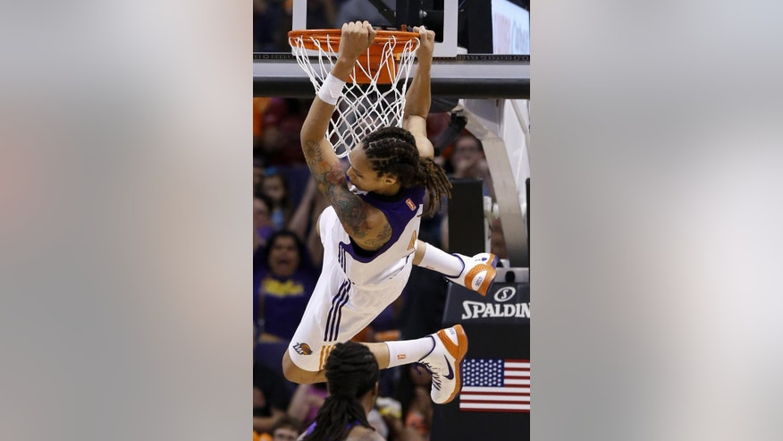 "FILE - In this May 27, 2013, file photo, Phoenix Mercury's Brittney Griner hangs on the rim after making a two-handed dunk against the Chicago Sky in the second half during a WNBA basketball game in Phoenix. Griner's busy WNBA offseason included competing in China, her first vacation in Miami and courtside seats to watch favorite player LeBron James. The slam-dunking Griner can add published author to her list of achievements with ""In My Skin,"" which chronicles her love of basketball and struggles with bullying, sexuality and family acceptance.  (AP Photo/Ross D. Franklin, File)"