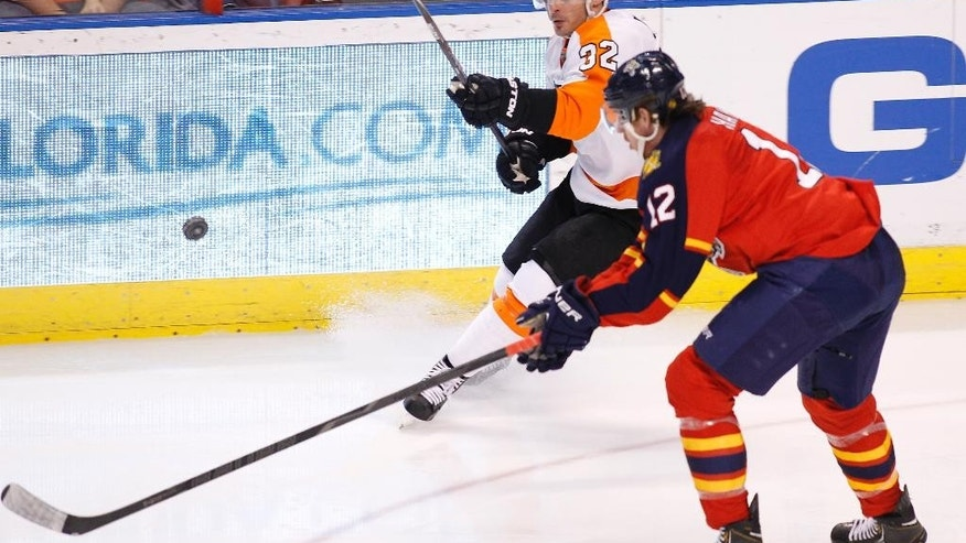 Philadelphia Flyers defenseman Mark Streit (32) and Florida Panthers right wing Jimmy Hayes (12) fight for the puck during the second period of an NHL hockey game in Sunrise, Fla., on Tuesday, April 8, 2014. (AP Photo/Terry Renna)