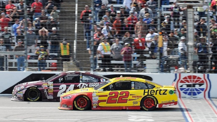 Joey Logano (22) begins a last lap pass by Jeff Gordon (24) during the NASCAR Sprint Cup series auto race at Texas Motor Speedway, Monday, April 7, 2014, in Fort Worth, Texas. Logano went on to win the race. (AP Photo/Larry Papke)