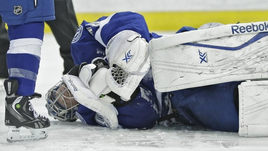 Tampa Bay Lightning goalie Ben Bishop rolls on the ice after injuring his shoulder against the Toronto Maple Leafs during the first period of an NHL hockey game Tuesday, April 8, 2014, in Tampa, Fla. (AP Photo/Chris O'Meara)