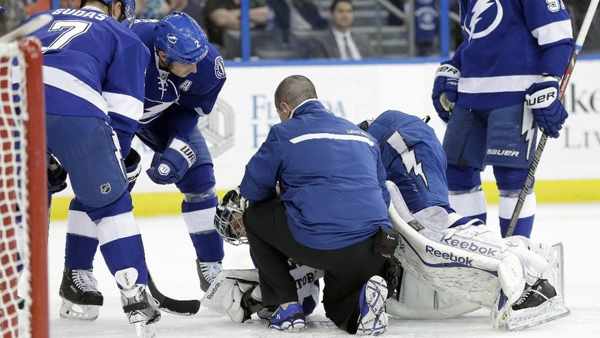 Tampa Bay Lightning defenseman Radko Gudas (7), of the Czech Republic, defenseman Eric Brewer (2) and center Steven Stamkos (91) look on as head athletic trainer Tommy Mulligan helps goalie Ben Bishop after he was injured during the first period of an NHL hockey game against the Toronto Maple Leafs Tuesday, April 8, 2014, in Tampa, Fla. Bishop left the game. (AP Photo/Chris O'Meara)