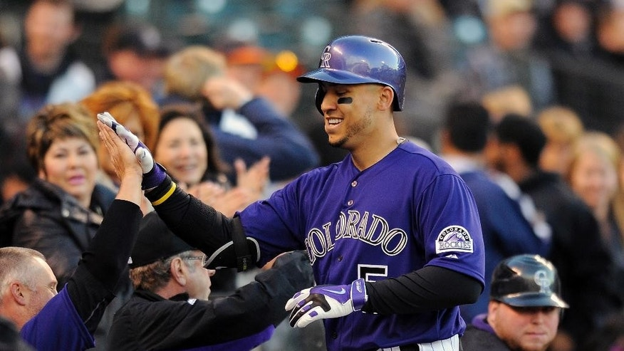Colorado Rockies Carlos Gonzalez celebrates after hitting a solo home run in the first inning of a baseball game against  the Chicago White Sox on Monday, April 7, 2014, in Denver.(AP Photo/Chris Schneider)