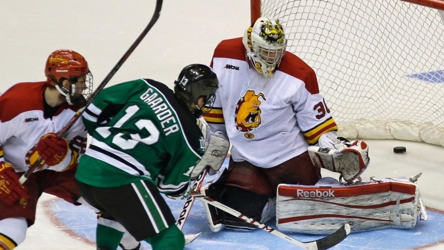 CORRECTS TO SAY THE FROZEN FOUR HOCKEY TOURNAMENT BEGINS APRIL 10 IN PHILADELPHIA - FILE - In this March 29, 2014 file photo, North Dakota forward Connor Gaarder (13) scores the winning goal past Ferris State goalie CJ Motte (30) in the second overtime period of a regional final of the NCAA college hockey tournament in Cincinnati. North Dakota won 2-1. Gaarder was well on his way to a career in NCAA Division III hockey when he accepted a last-minute invitation to walk on at the UND. He has become one of UND's favorite supporting cast members in a season that will culminate in this week's Frozen Four beginning April 10 in Philadelphia.  (AP Photo/Al Behrman, File)