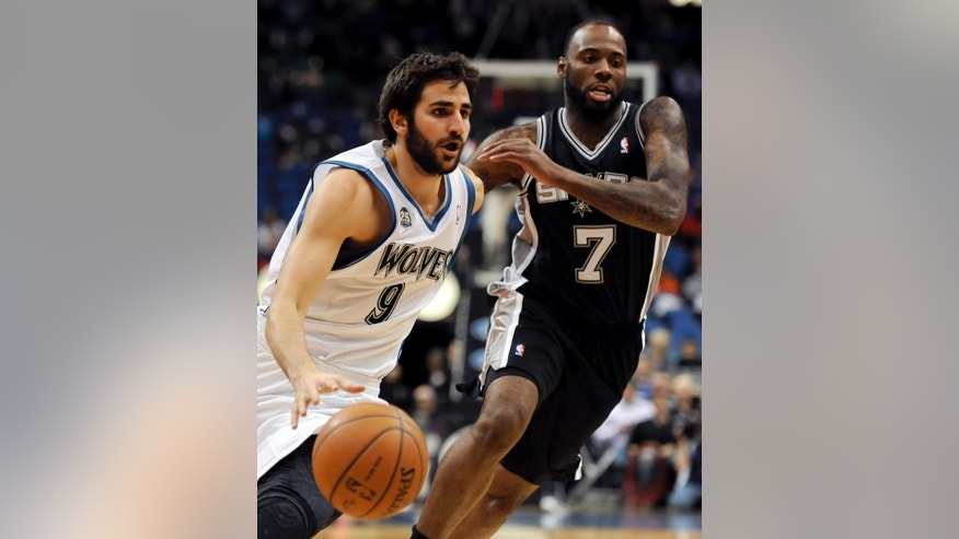 Minnesota Timberwolves' Ricky Rubio (9), from Spain, drives against San Antonio Spurs' Damion James (7) during the fourth quarter in an NBA basketball game at the Target Center on in Minneapolis on Tuesday, April 8, 2014. Timberwolves won 110-91. (AP Photo/Hannah Foslien)