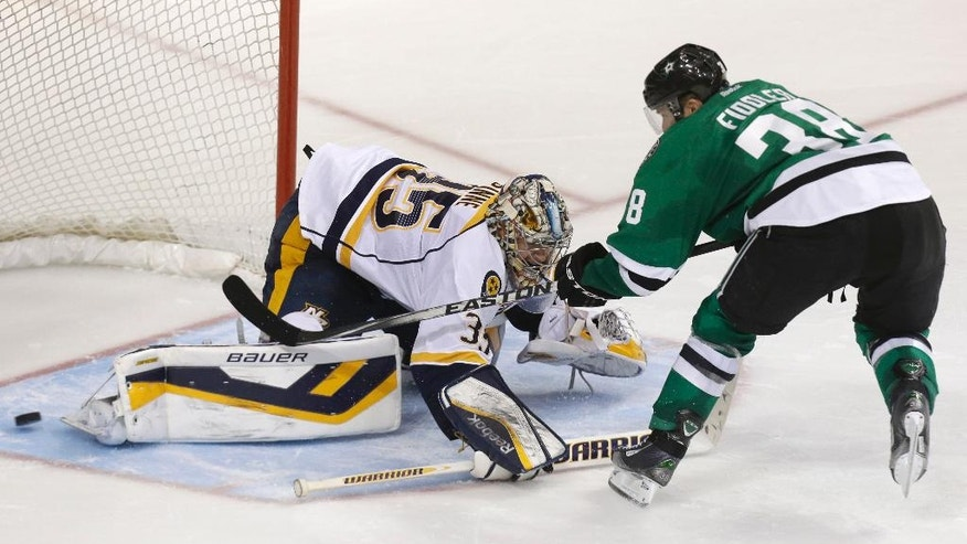 Dallas Stars center Vernon Fiddler (38) gets the puck past Nashville Predators goalie Pekka Rinne (35) during an overtime shootout in an NHL hockey game Tuesday, April 8, 2014, in Dallas. Dallas won 3-2. (AP Photo/LM Otero)