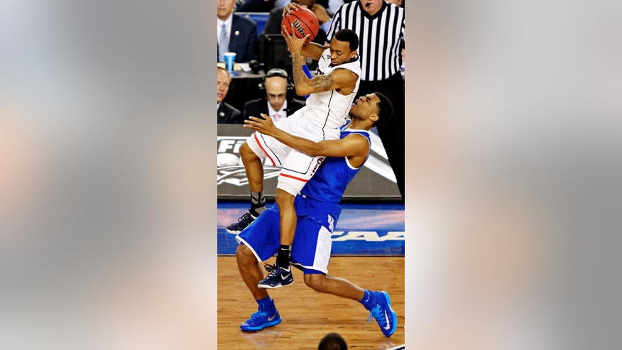Connecticut guard Ryan Boatright, top, lands on top of Kentucky guard Andrew Harrison during the second half of their NCAA Final Four championship game Monday, April 7, 2014 at AT&T Stadium in Arlington, Texas. (AP Photo/The Dallas Morning News, Tom Fox)