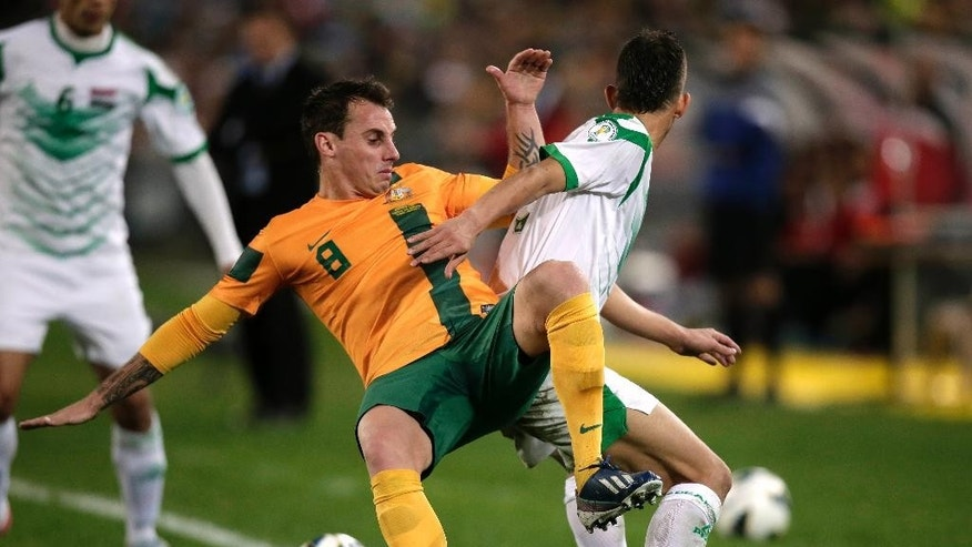 FILE - In this June 18, 2013, file photo, Australia's Luke Wilkshire, left, is pushed off the ball by Iraq's Mustafa Kareem during their World Cup soccer Asian qualifying match at the Sydney Olympic Stadium in Sydney, Australia. (AP Photo/Rick Rycroft)